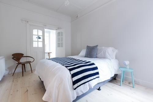Crisp white Danish stylish bedroom with striped throw rug and blue side table