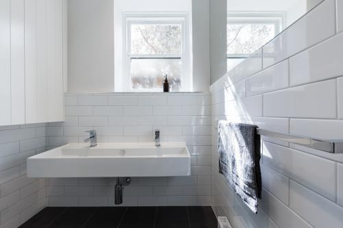 Double basin vanity in modern white renovated bathroom in heritage building horizontal