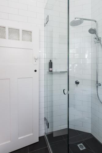 Modern white shower in bathroom renovation with brick pattern subway style tiling