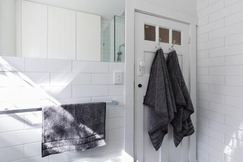 Luxury towels on door hooks in modern white bathroom with brick pattern subway tiles