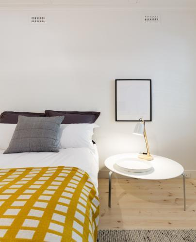 Bedroom decor details of yellow throw rug and bedside table with lamp