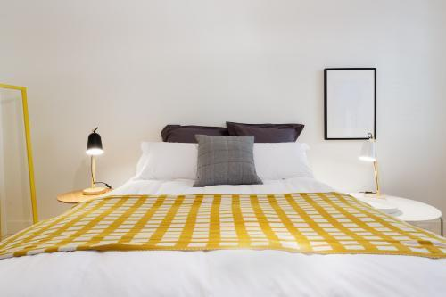 Yellow accent decor throw rug in contemporary styled white bedroom