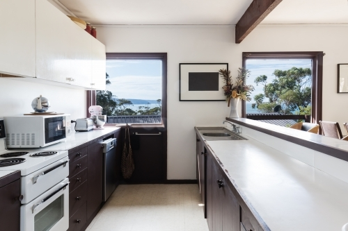 Older style retro 70s kitchen in Australian beach house with a view