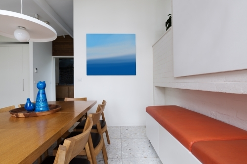 Orange leather bench seat along scandinavian styled dining room interior with blue accents