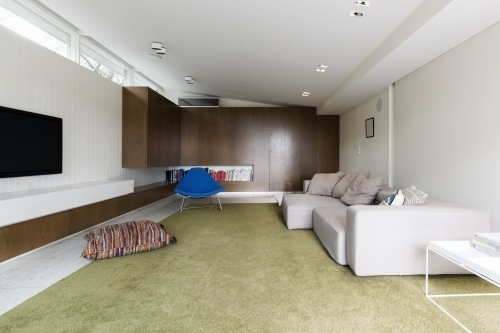 Modern living room with custom walnut cabinetry and large green wool rug