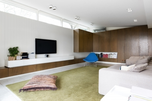 Scandinavian styled contemporary living room with walnut built in cabinets