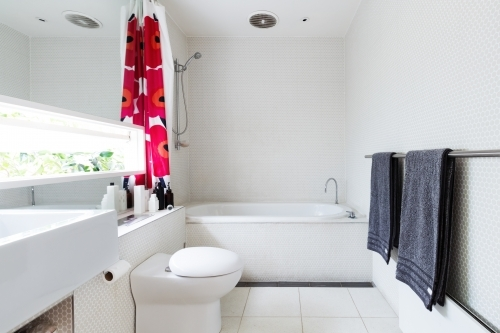 Contemporary white bathroom of mosaic and terrazzo tiles with red shower curtain