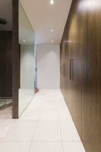 Huge walk through wardrobe with walnut doors hallway in luxurious Australian home