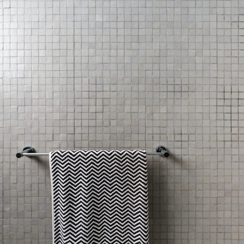 Background of mosaic square wall tiles with chevron towel on chrome towel rail
