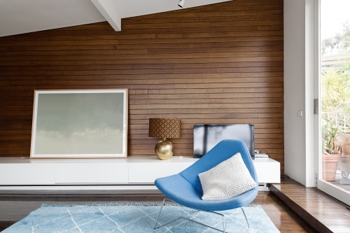 Horizontal wood panelling and blue chair in mid century living room