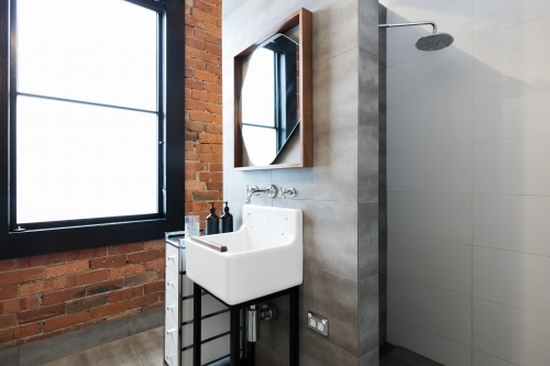 Renovated warehouse bathroom with vintage basin and walk in shower