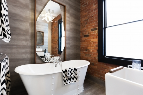 Freestanding vintage style white bath tub in renovated warehouse apartment