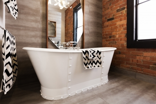 Close up of white freestanding bath tub in vintage interior style bathroom