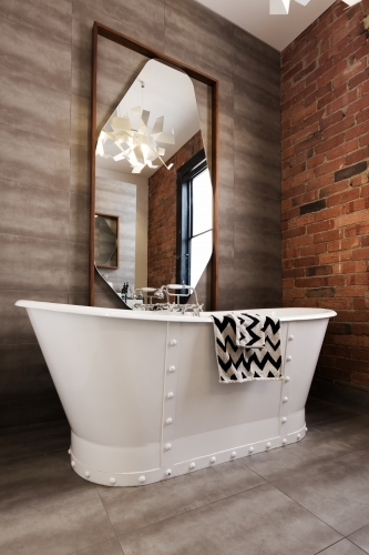 Classic white freestanding iron look bathtub in vintage style renovated bathroom