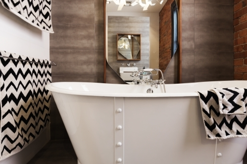 White free standing vintage style bath tub with chevron pattern black and white towels