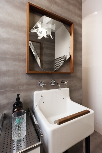 White vintage vanity basin with mirror against grey tiled wall