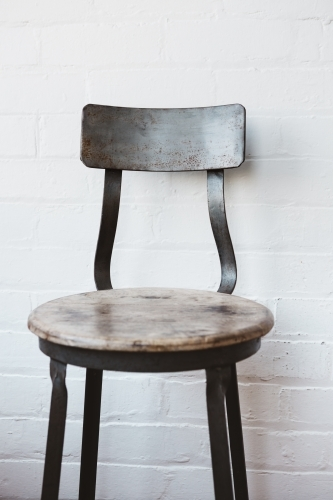 Rustic cafe chair against painted white brick wall
