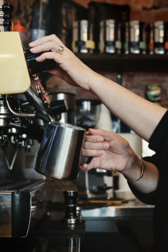 Woman barista making espresso coffee and frothing milk with steam