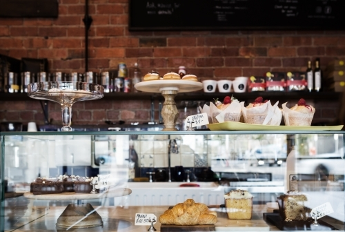 Horizontal cake display case in cafe with rustic wall behind