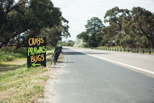Roadside sign advertising fresh crays prawns and bugs for sale horizontal
