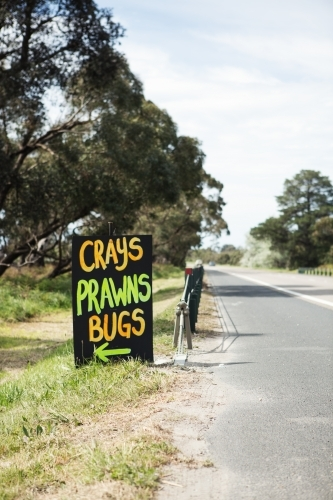 Roadside sign advertising fresh crays prawns and bugs for sale vertical