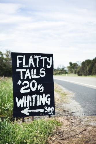 Black and white roadside sign advertising flathead tails vertical