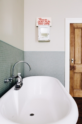 Vintage style bathroom with quirky retro safety sign on an old medicine cabinet
