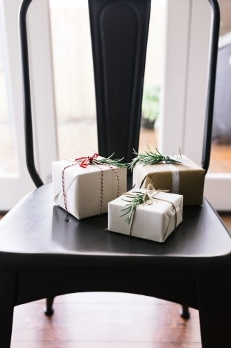 Christmas gifts beautifully wrapped on a contemporary dining chair