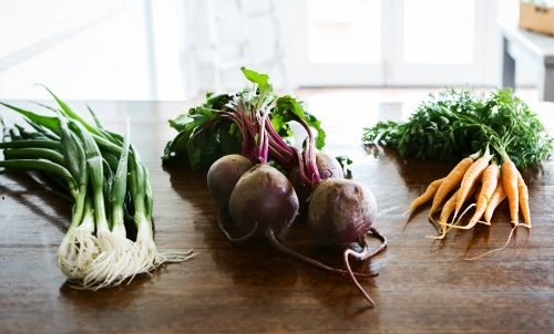 Spring onions, beetroot and carrots on a wooden kitchen bench