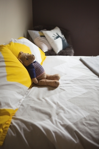 Cute toy teddy bear on the bed in a vintage styled guest bedroom