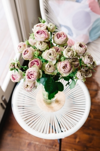 Beautiful vase of vintage style cabbage roses in a contemporary home