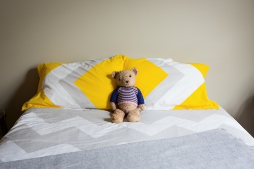 Old teddy bear alone on a double bed