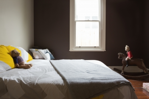 Kids bedroom with soft toys and a dark painted wall