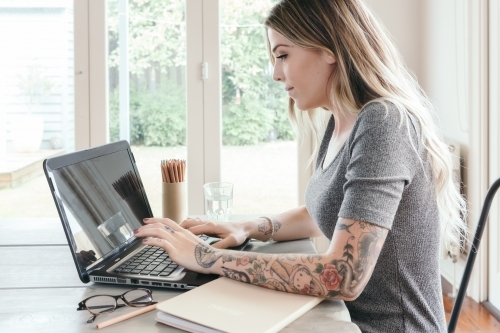 Girl with tattoos typing on computer keyboard at home