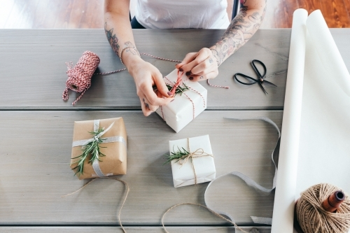 Overhead view of young girl wrapping Christmas presents in natural papers and twine