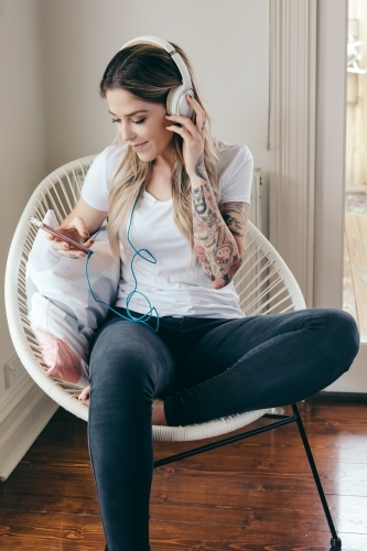 Girl listening to music on her smartphone at home