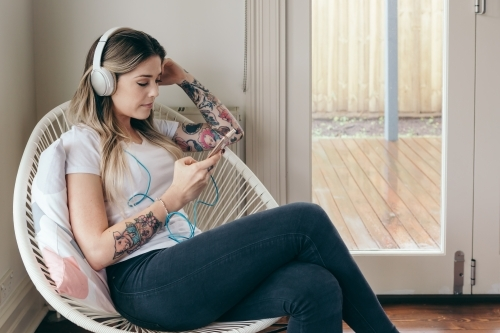 Girl with tattoos creating a playlist on her smart phone