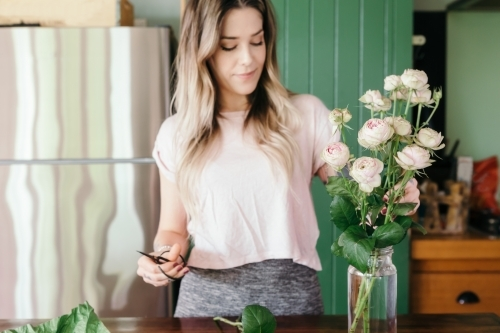 Focus on the pink roses with blurred woman in background cutting stems and arranging