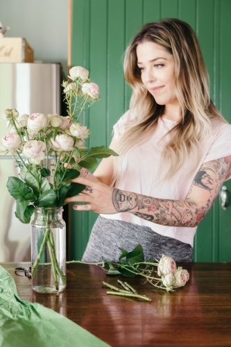 Girl with cute arm tattoos arranging pretty pink roses