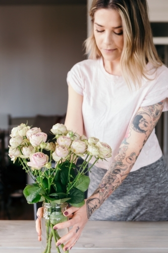 Stylist placing a vase of pink roses as a table centre piece