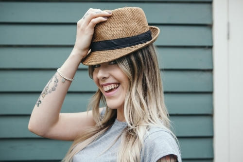 Gorgeous fashionable girl playfully putting on a hat
