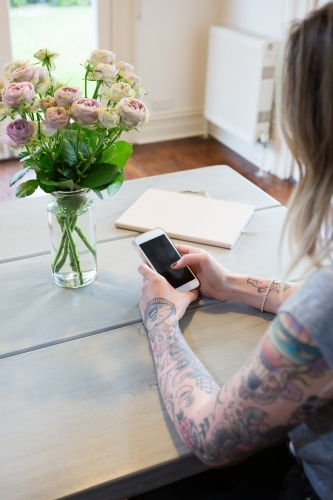 Gen Y with tattoos using a mobile phone at home
