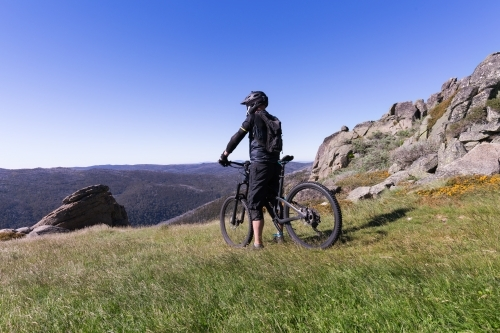 Guy looking at the view on a mountain bike at Thredbo in summer