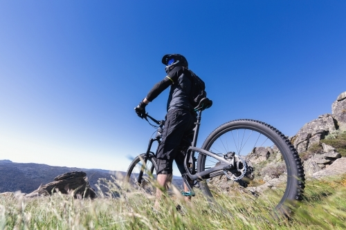 Man standing on top of Mt Kosciuszko with his mountain bike