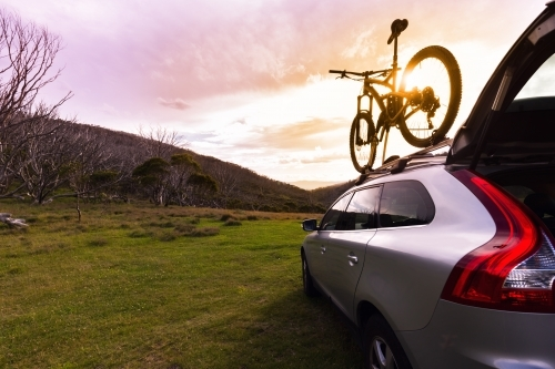 SUV and mountain bike with mountain view and sunflare