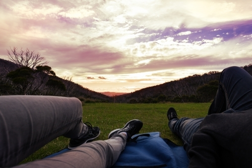Point of view of couple lying on a rug watching the sunset