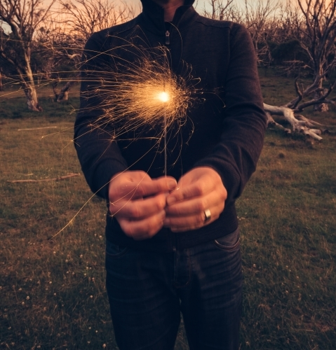 Guy holding a sparkler to camera on a mountain top at dusk
