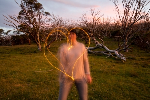 Woman making a heart shape with a sparkler at dusk