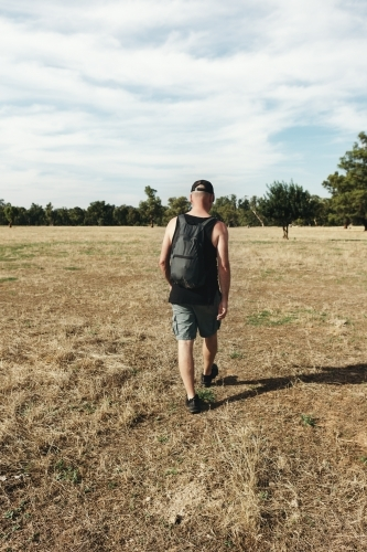Hiker walking through a dry paddock of grass