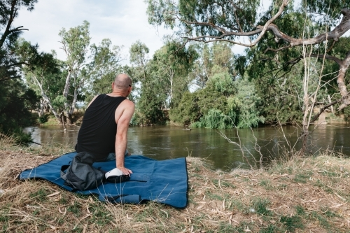 Man sitting on a rug next to a river in the bush